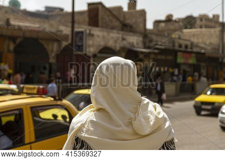 A Syrian Man Wearing Local Traditional Clothes Is Standing By A Busy Road In The Historic District O