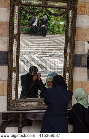 Damascus, Syria 03-28-2010: A Young Arabic Woman Is Standing In Front Of A Mirror Putting On Niqab M
