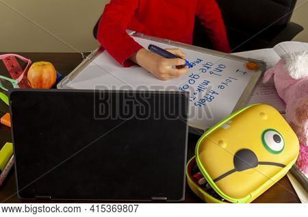 A Cute Little Girl Is Writing Sentences On A White Board Using Blue Marker. She Is Attending Virtual