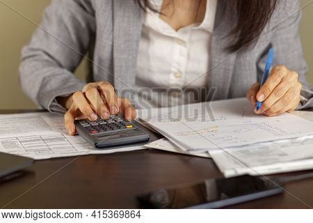 A Business Woman Wearing Formal Dress Is Working At An Office Setting. She Is Calculating Income And