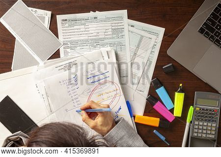 A Caucasian Woman Is Filling 1040 Federal Income Tax Return Forms. She Is Calculating Her Income And