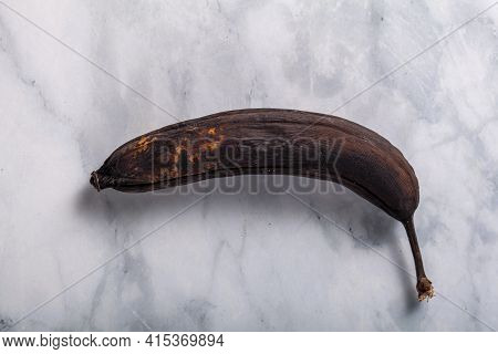 Flat Lay Image Of A Banana In Its Skin. The Peel Is Covered With Dark Spots Indicating Over Ripening