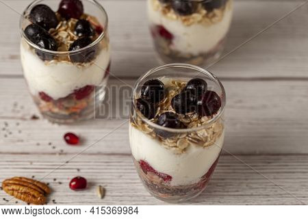 Angled View Of Delicious Fruit Yogurt Parfait  Cups Filled With Layers Of Muesli, Chia Seeds, Fresh