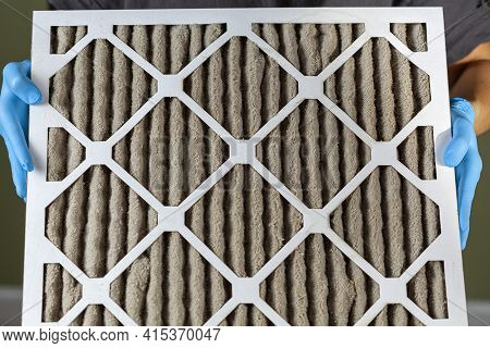 A Person Wearing Blue Gloves Is Holding A Heavily Clogged Dirty Air Filter In Hands Before Replacing
