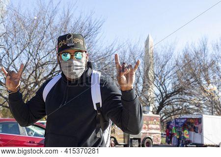 Washington Dc, Usa 11-29-2020: A Young Hispanic Man Wearing Baseball Hat, Polarized Designer Sunglas