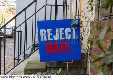 A Blue Yard Sign That Says Reject Hate Is Placed On The Front Yard Of An Old Building Ahead Of Us El