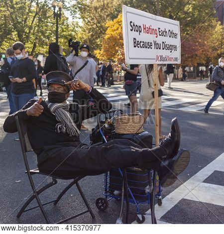 Washington Dc, Usa 11/06/2020: An Elderly African American Man Is Sitting Next To A Banner That Says
