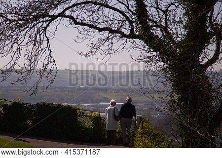 Well Dressed Elderly Couple Is Enjoying The Panoramic View Of Bristol And The Countryside,  As Seen