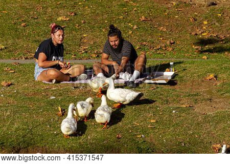 Frederick, Md, Usa 10/14/2020: A Young Couple In Summer Clothes Are Sitting On Picnic Blanket On A S