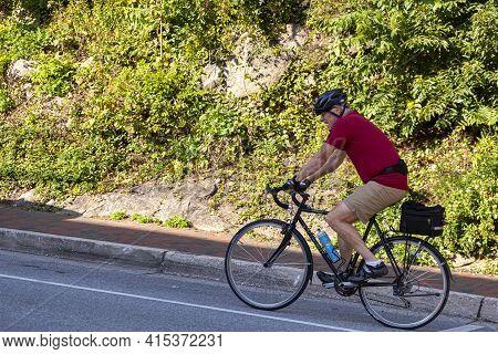 Ellicott City, Md, Usa 10/07/2020: An Elderly Caucasian Man Wearing Helmet Is Cycling Uphill On The