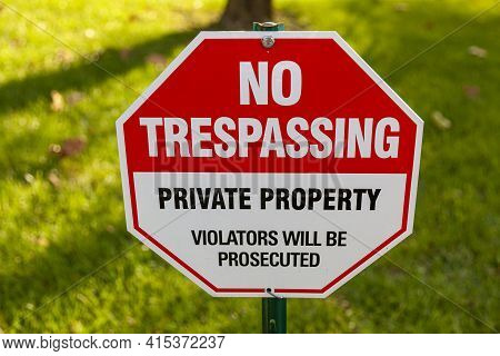 Close Up Isolated Image Of A Metal Red And White Octagonal  Warning Yard Sign That Says