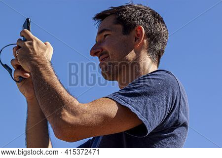 Great Falls, Va, Usa 10/03/2020: A Caucasian Man With Short Hair And Short Beard Is Holding A Smartp