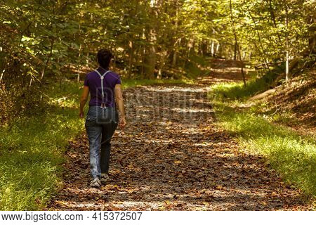 A Woman Wearing Jeans With Suspenders Is Walking Alone In A Hiking Trail Covered With Fallen Autumn