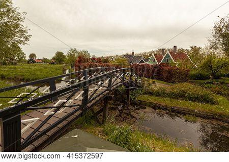 Landscape Image Of A Small Village Near Hague, Netherlands With A Tiny Creek, Grassland, Shrubs, Tre