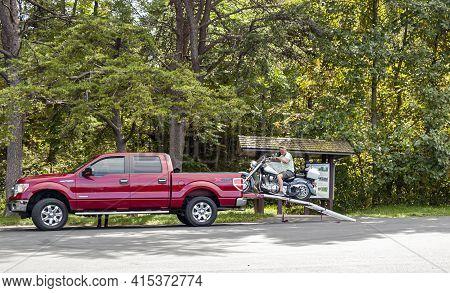 Shenandoah Valley, Va, Usa 09/27/2020: An Elderly Motorist Is Unloading His Motorbike From The Trunk