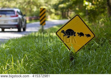 A Road Sign At A Wildlife Refuge That Warns The Drivers Of Wild Animals Crossing The Road. It Aims T