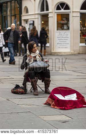 Bath, Uk, 03/06/2010: A Young Woman Musician Is Sitting On A Foldable Stool In A Crowded Street And