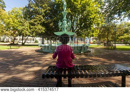 A Little Girl Wearing Pink Casual Clothing Is Sitting Alone On A Metal Bench In The Fountain Park Of