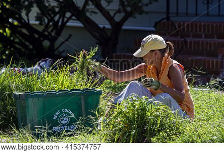 Chestertown, Md, Usa 08/30/2020 :a Woman Wearing Hat Is Sitting On Grass And Pulling Weeds From Her