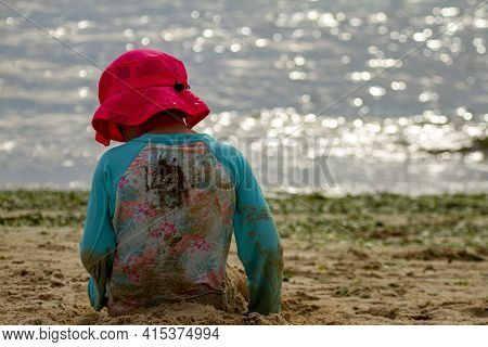 A Young Girl Wearing Long Sleeve Rash Guard Swim Suit And A Sun Hat Is Playing Alone On A Sandy Beac