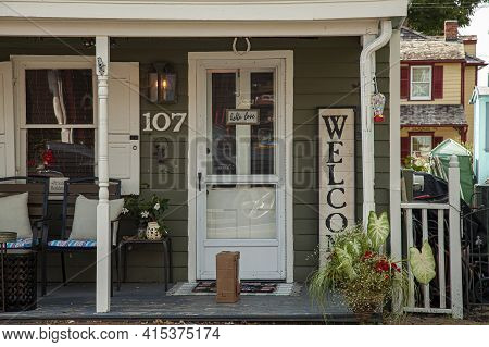 Chesapeake City, Md 08/25/2020: Front Porch Of An 19th Century Traditional House With White Wooden D