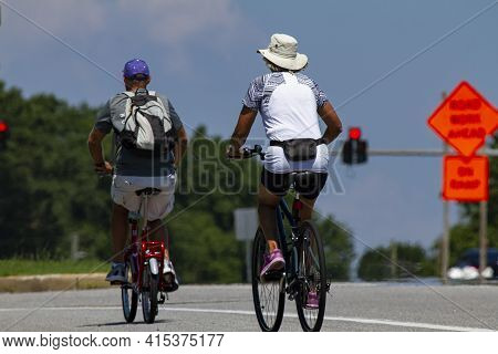 A Senior Couple Wearing Casual Shorts And T Shirts As Well As Hats Is Riding Bikes Near A Highway On