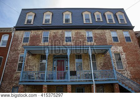 A Run Down Large Vintage House With Discolored Brick Exterior Located In The Historic District Of An
