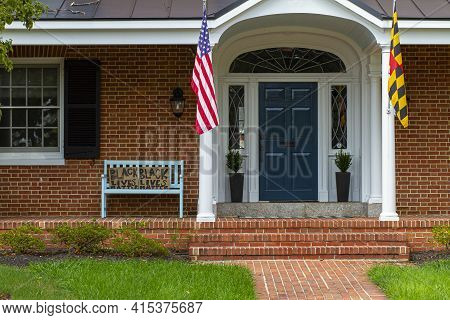 Frederick, Md 08/14/2020: A Traditional Brick House With An American And A Maryland Flag On Flag Pos