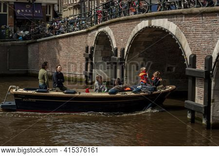 Amsterdam, Netherlands, 05/15/2010: Close Up Image Of A Family Including Kids And Adults On A Small