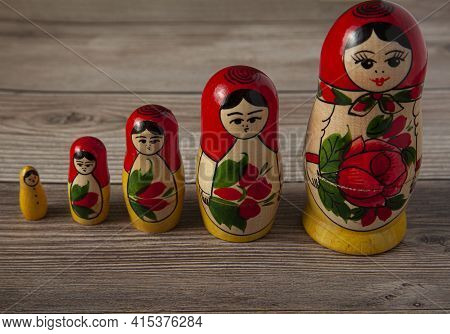 A Line Up Of Handmade Russian Matrushka Dolls On Wooden Background. These Folkloric Women Figurines