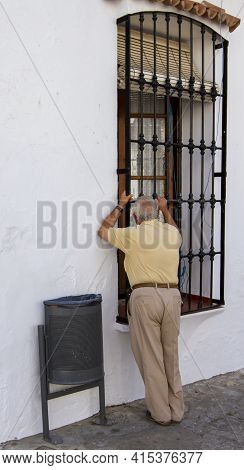 A Creepy Old Man Is Looking Inside A House On The Street Through The Metal Window Guards. His Intent