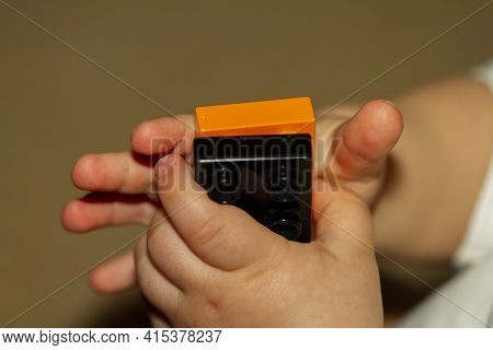 Close Up Image Of An Infant Baby's Hands As He Or She Is Trying To Interlock Two Toy Bricks. Image I