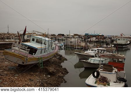 A Very Rundown Fishing Harbor In Northern Syrian City Of Tartus. Small Fishing Boats And Motor Boats