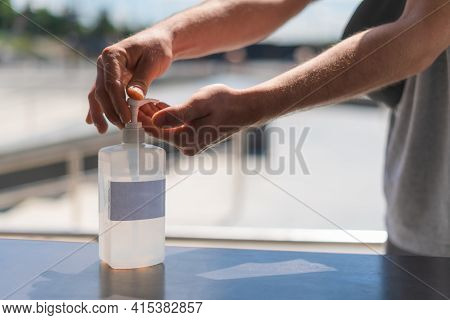 Person Using Hand Sanitizer Gel In Public. Hand Pressing Antibacterial Lotion Bottle Outside. Close
