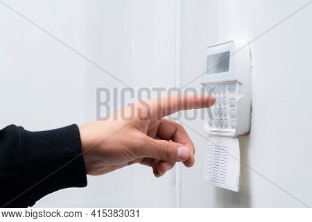 Hand Entering Alarm System Password Of An Apartment, Home Or Business Office. Surveillance And Prote