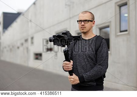 Professional Male Videographer Holding Dslr Camera On 3-axis Gimbal Over Grey Concrete Wall