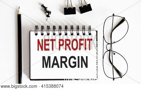 Net Profit Margin Notepad Writing On White Background With Pencil And Glasses