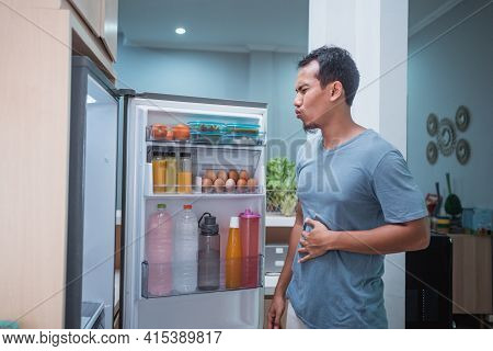 Man Hold His Belly While Open The Fridge Door Looking Something To Eat