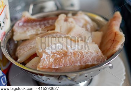 Defrosting Of Fish Fillets, Atlantic Cod In A Pot On A Plate Ready For Frying