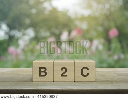B2c Letter On Block Cubes On Wooden Table Over Blur Pink Flower And Tree In Garden, Business To Cust