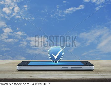 Security Shield With Check Mark Flat Icon On Modern Smart Mobile Phone Screen On Wooden Table Over B