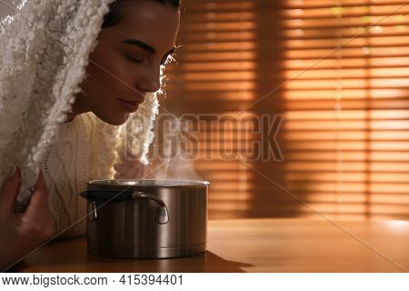 Woman With Plaid Doing Inhalation Above Saucepot At Table Indoors. Space For Text