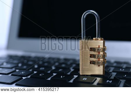 Metal Code Padlock On Laptop Keyboard, Space For Text. Cyber Security Concept