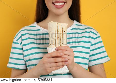 Happy Young Woman Holding Tasty Shawarma On Yellow Background, Closeup