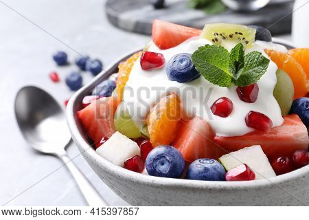 Delicious Fruit Salad With Yogurt In Bowl On Table, Closeup