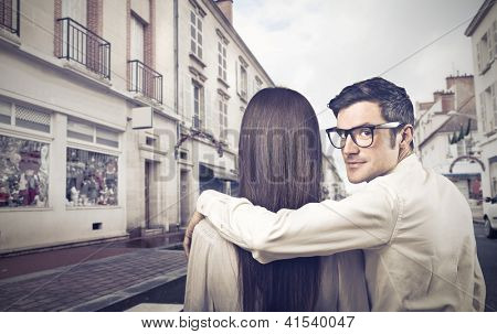 A man holds his arm on the shoulders of a woman and look at the lens behind them on a city street