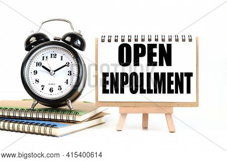 Open Enrollment. Text On White Notepad Paper On A Stand Next To Our Desk Clock On A Sideboard. On Wh