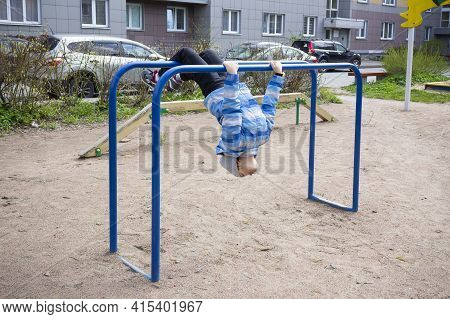 Child In Blue Jacket In Playground Hanging On Bars Upside Down