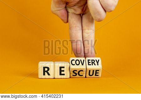 Recovery And Rescue Symbol. Businessman Turns Cubes And Changes The Word 'recovery' To 'rescue'. Bea