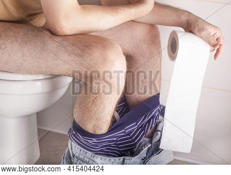 Man Sitting On Toilet Bowl At Home Or Hotel, With Toilet Paper Roll In Hands. Abdominal Stomach Ache